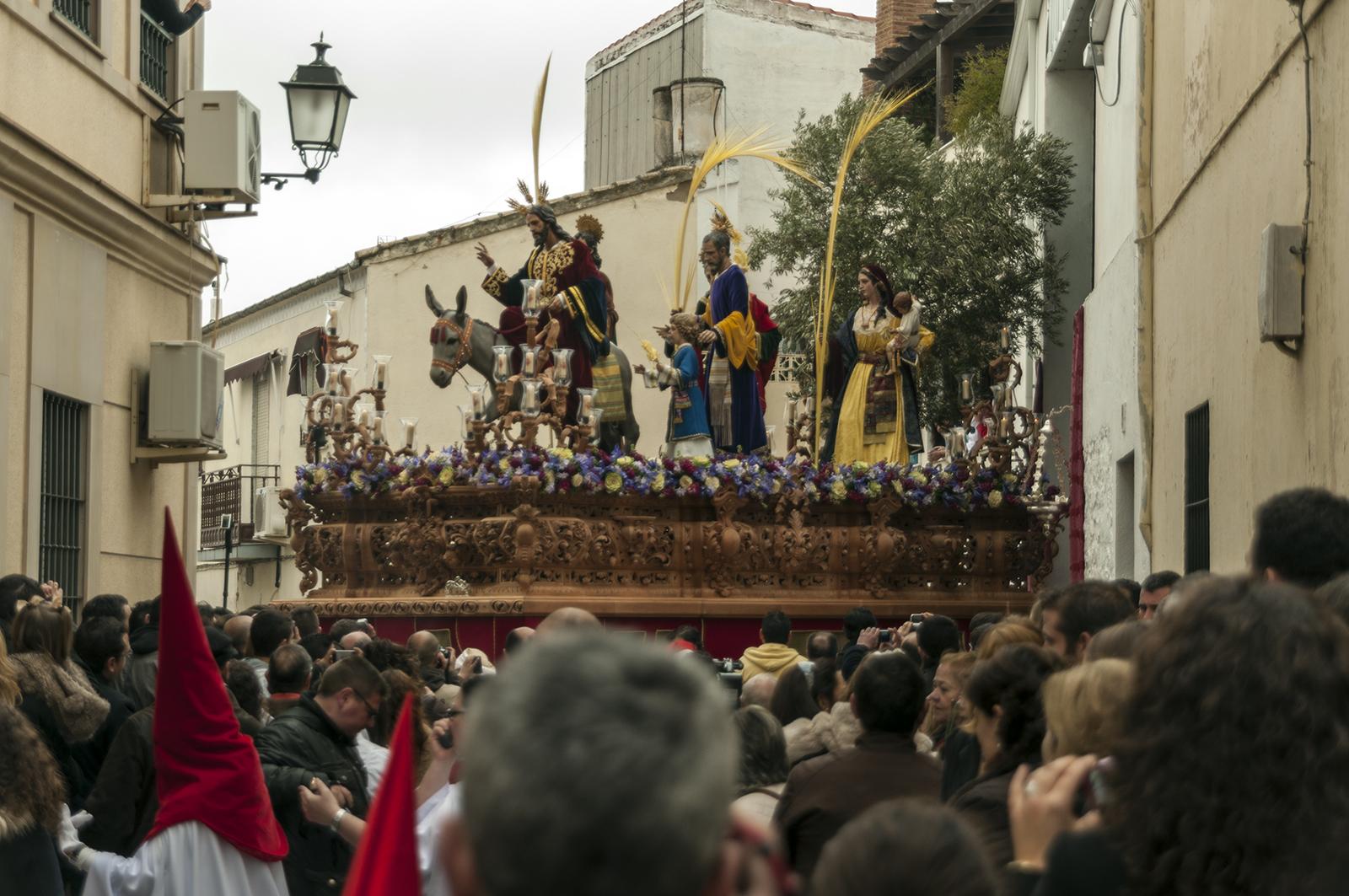 Jesús de Nazaret a lomos de un asno | Foto del paso de misterio de la Entrada en Jerusalén saliendo a la calle rodeada de público.